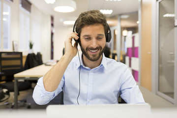 Smiling Businessman in the office on video conference, headset,