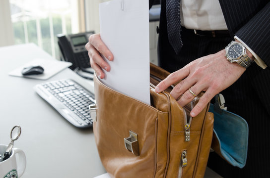 Business man hand puts some  documents in his bag