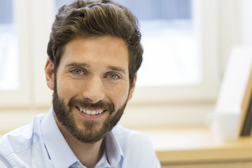 Portrait of handsome bearded man in office. looking at camera