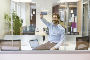 Selfie casual businessman taking pictures in open space office
