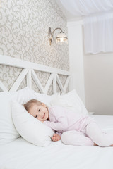 Little child girl in soft bed
