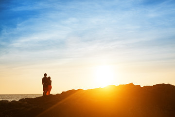 Couple sit on the rock and wait for sunset