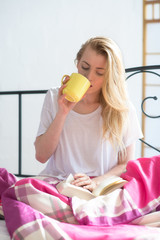 Frau sitzt im Bett mit Buch und Kaffee