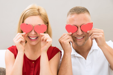 Couple Covering Eyes With The Hearts