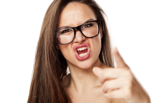 angry beautiful woman with glasses, shouting and pointing at you