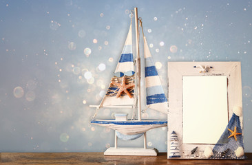 vintage nautical frame with wooden boat on wooden table and glit