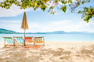 Empty beach chairs on a sunny day at Rang Yai iland, Thailand