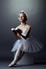 Smiling little ballerina posing sitting on cube