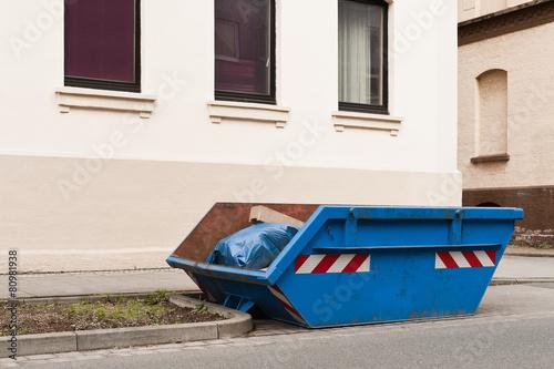 ein blauer container f r abfall steht vor einem wohnhaus stockfotos und lizenzfreie bilder auf. Black Bedroom Furniture Sets. Home Design Ideas