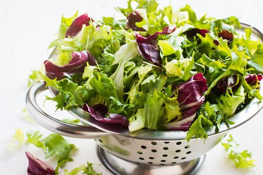 Fresh green salad wix  in metal colander on white background