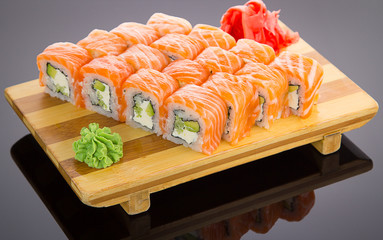 Japanese tasty sushi set on a wooden plate over black background