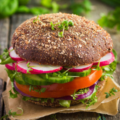 Healthy fast food. Vegan rye burger with fresh vegetables