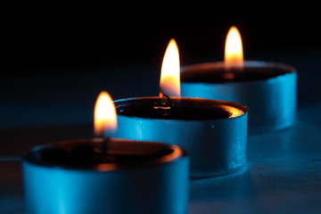 Three blue candles are glowing in the darkness