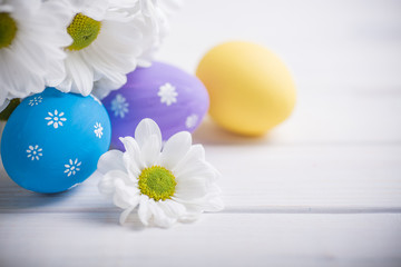 Easter colored eggs with flowers on white wooden background