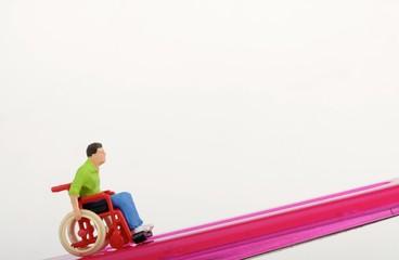miniatura di invalido in sedia a rotelle in salita