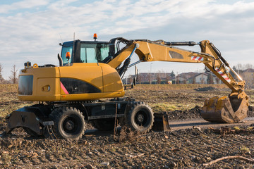 yellow excavator with muddy shovel on building site