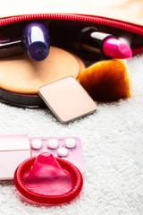 Pills, condom and cosmetics in handbag.