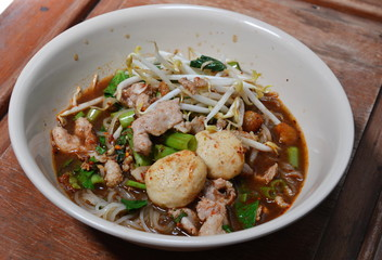 noodle topping with pork ball in black spicy soup