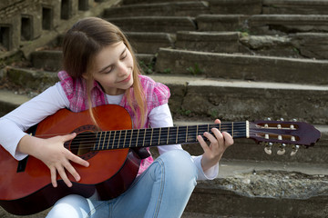 Cute Young Girl Playing a Guitar Against Old Stone Staircase