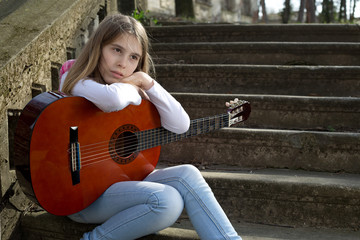 Pensive Young Girl with Guitar in Her Lap Sitting on the Stairs