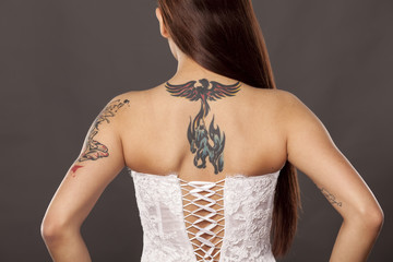 back view of pretty woman with tattoos posing in white corset