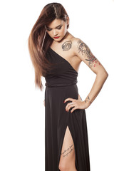 pretty young woman with tattoos posing in a dress on a white
