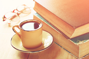 coffee cup, stack of old books and reading glasses over wooden t