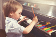 Young boy painting piano keys. Fine arts and music.