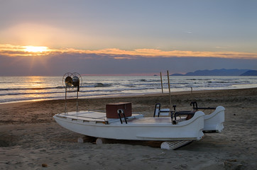 small fiberglass fishing boat on the beach at sunset