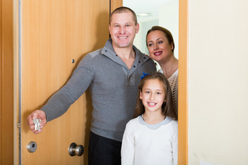 family of three opening door of new apartment