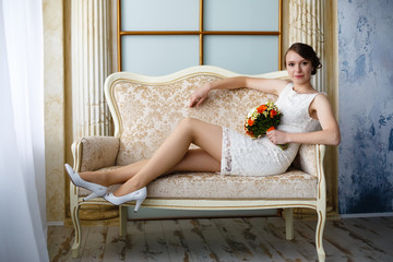 young beautiful sexy woman with flowers in a chair on a couch