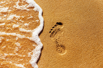 Close-up textured image of a foot print on a yellow sand at a se