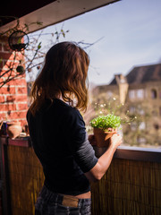 Woman attending to her plants on balcony