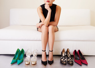 Woman thinking on sofa with many shoes.Shopping
