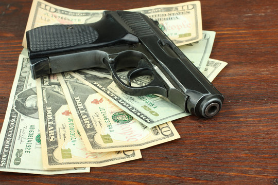 gun and money on a wooden background