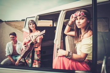 Young hippie friends with guitar on a road trip