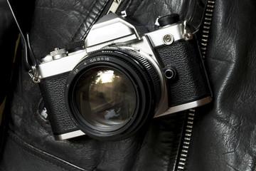 Old analog film camera and leather jacket