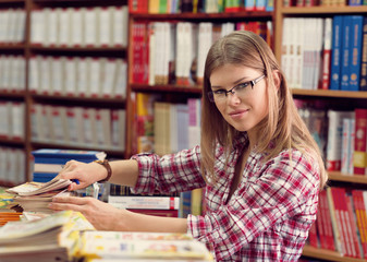 Female small business owner arranging magazines in bookstore