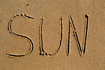 The word sun drawn in sand