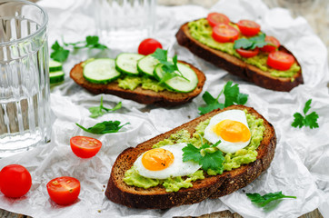 rye sandwiches and mashed avocado, eggs, tomatoes and cucumbers