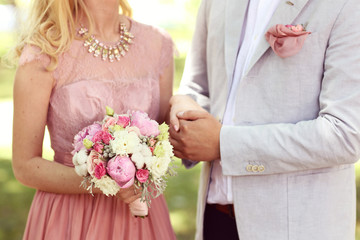 Couple holding hands, Woman with peonies bouquet