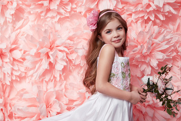 Beautiful little girl in cute dress with flower