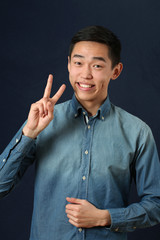 Smiling young Asian man giving the victory sign and looking at c
