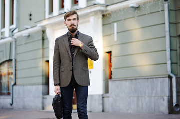 stylish man with a beard and mustache with a bag in hand on buil