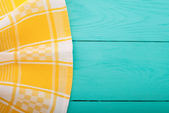 Yellow napkin on blue wooden background
