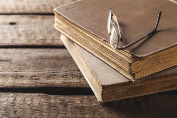 Antique. Old book and glasses on brown wooden planks background
