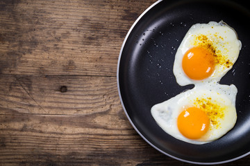 Keuken foto achterwand Gebakken Eieren two frying eggs in pan on table