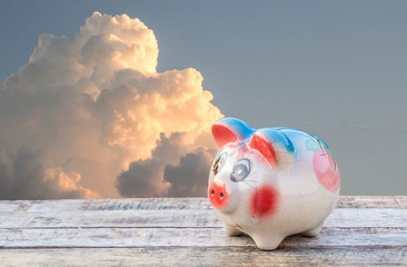 Piggy bank on wooden table over sky blurred background