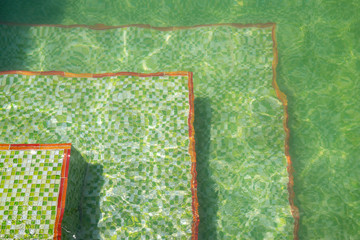 Floor of a swimming pool with ripples and green mosaic tile