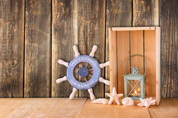 old nautical wood wheel, anchor and shells on wooden table over